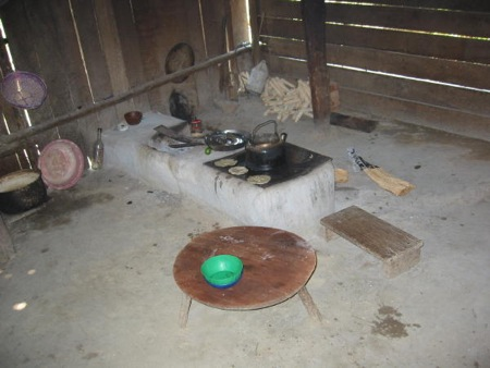 Maxiana's kitchen--dirt floor, a couple of bancos, and a comal for cooking tortillas. Most modern-day Kekchi women have their cooking fire built waist high.