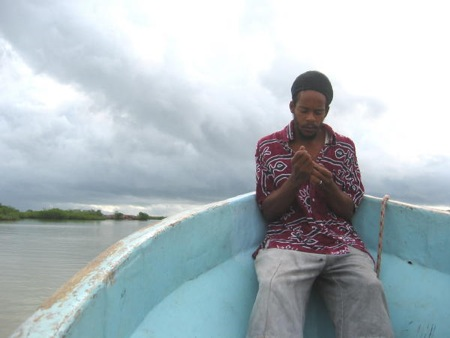 The skiff to Placencia and its Kriol deckhand.
